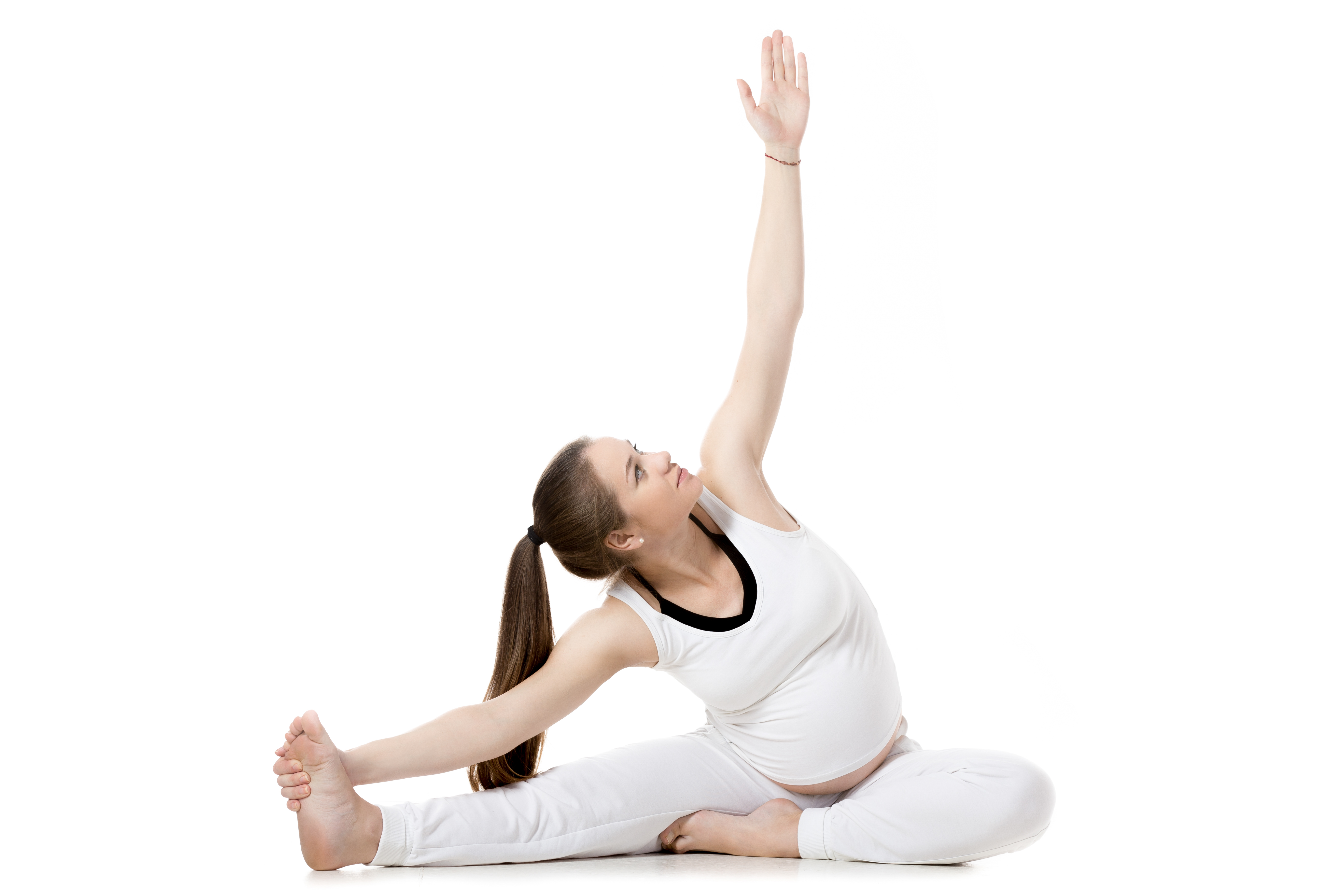 Full length portrait of young pregnant fitness model in sportswear warming up, doing yoga, pilates training, Janu Sirsasana, Seated Head-to-Knee Forward Bend Pose, white background, studio, isolated